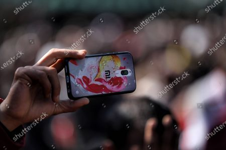 A worker clicks pictures with MI Redmi Phone while Jammu and Kashmir (PDP) Peoples Democratic Party President Mehbooba Mufti Addressing party workers during a rally in Baramulla, Jammu and Kashmir