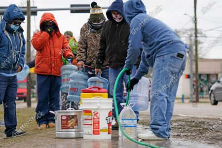 Stock Photo of Jose Blanco, right, fills a cooler with water from a park spigot as others wait in line, in Houston. Houston and several surrounding cities are under a boil water notice as many residents are still without running water in their homes