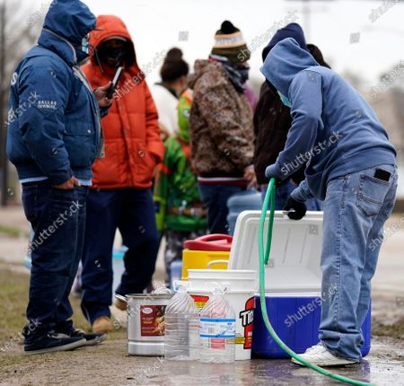 Jose Blanco, right, fills a cooler with water from a park spigot, in Houston. Houston and several surrounding cities are under a boil water notice as many residents are still without running water in their homes