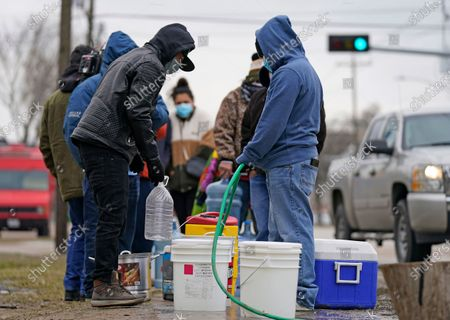 Jose Blanco, right, and Juan Lopez, left, fill containers with water from a park spigot, in Houston. Houston and several surrounding cities are under a boil water notice as many residents are still without running water in their homes