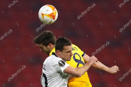 Tottenham's Harry Winks, background, jumps for a header with Wolfsberger's Michael Liendl during the Europa League round of 32, first leg, soccer match between Wolfsberger AC and Tottenham Hotspur at the Puskas Arena stadium in Budapest, Hungary