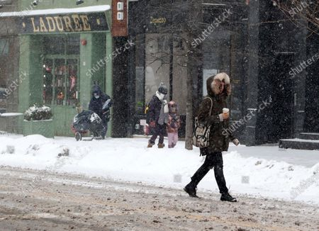 People walk through SOHO as snow falls in New York, New York, USA, 18 February 2021. The storm, which has caused large widespread power outages in Texas and other parts of the United States, is expected to drop several inches of snow in the New York area and other parts of the Eastern Seaboard.