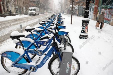A woman carrying groceries walks past a line of CitiBikes as she walks through SOHO as snow falls in New York, New York, USA, 18 February 2021. The storm, which has caused large widespread power outages in Texas and other parts of the United States, is expected to drop several inches of snow in the New York area and other parts of the Eastern Seaboard.