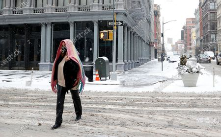 A woman wearing a scarf over her head walks through SOHO as snow falls in New York, New York, USA, 18 February 2021. The storm, which has caused large widespread power outages in Texas and other parts of the United States, is expected to drop several inches of snow in the New York area and other parts of the Eastern Seaboard.