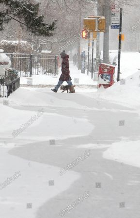 A person crosses a street as snow falls in New York, New York, USA, 18 February 2021. The storm, which has caused large widespread power outages in Texas and other parts of the United States, is expected to drop several inches of snow in the New York area and other parts of the Eastern Seaboard.