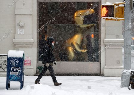 A man walks past the Coach store in SOHO crosses as snow falls in New York, New York, USA, 18 February 2021. The storm, which has caused large widespread power outages in Texas and other parts of the United States, is expected to drop several inches of snow in the New York area and other parts of the Eastern Seaboard.