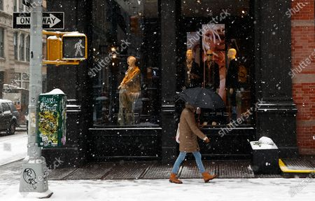 A woman with an umbrella walks through SOHO as snow falls in New York, New York, USA, 18 February 2021. The storm, which has caused large widespread power outages in Texas and other parts of the United States, is expected to drop several inches of snow in the New York area and other parts of the Eastern Seaboard.