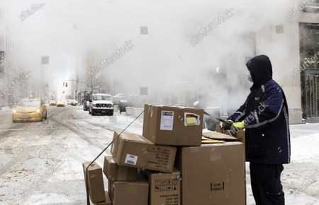 A FedEx delivery person waits to cross a snowy street during a storm in New York, New York, USA, 18 February 2021. The storm, which has caused large widespread power outages in Texas and other parts of the United States, is expected to drop several inches of snow in the New York area and other parts of the Eastern Seaboard.