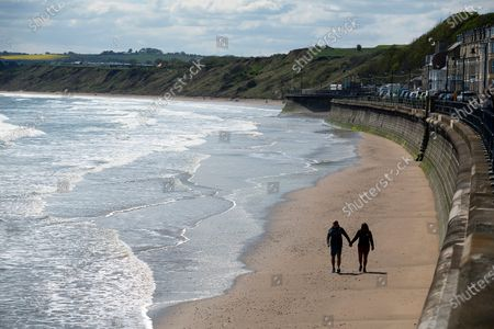 Stock Picture of A couple ( Mark Allitt,58,retired & Sarah Mason, 51,a NHS medical receptionist & key worker) walk hand in hand on the beach at Filey in North Yorkshire.