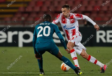 Red Star's Milan Rodic, right, duels for the ball with AC Milan's Pierre Kalulu during the Europa League round of 32 first leg soccer match between Red Star and AC Milan at the Rajko Mitic Stadium in Belgrade, Serbia