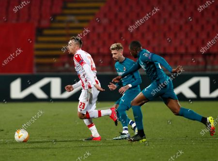 Red Star's Milan Rodic, left, duels for the ball with AC Milan's Samu Castillejo, centre, and AC Milan's Pierre Kalulu during the Europa League round of 32 first leg soccer match between Red Star and AC Milan at the Rajko Mitic Stadium in Belgrade, Serbia