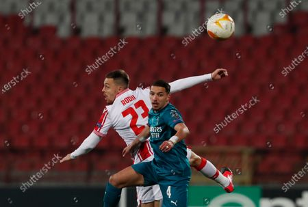 Milan's Ismael Bennacer, front, duels for the ball with Red Star's Milan Rodic during the Europa League round of 32 first leg soccer match between Red Star and AC Milan at the Rajko Mitic Stadium in Belgrade, Serbia