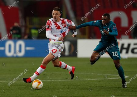 Red Star's Milan Rodic, left, duels for the ball with AC Milan's Pierre Kalulu during the Europa League round of 32 first leg soccer match between Red Star and AC Milan at the Rajko Mitic Stadium in Belgrade, Serbia