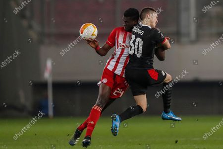 Olympiacos' Ousseynou Ba, left, challenges for the ball with PSV's Ryan Thomas during a Europa League, round of 32, first leg soccer match, between Olympiacos and PVS at Georgios Karaiskakis stadium in Piraeus port, near Athens