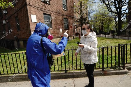 A view of a volunteer giving out free masks and nitrile gloves in Main St, Flushing Queens, New York, USA during Coronavirus pandemic on May 2, 2020.