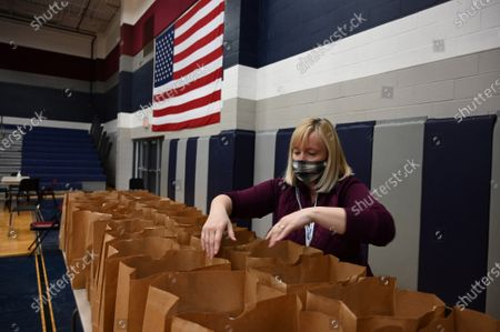 A volunteer fills bags with meals for people displaced by the winter storm at a shelter in Wylie, Texas Thursday, February, 18, 2021. Record cold temperatures along with snow and ice caused power outages resulting in frozen water pipes. May parts of the state are under a boil water order due low water pressure.
