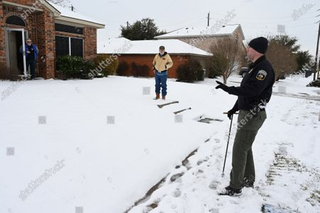 A police officer checks on residents in Wylie, Texas Thursday, February, 18, 2021. Officers helped turn off water in homes that had frozen or broken pipes. Record cold temperatures along with snow and ice caused power outages resulting in frozen water pipes. May parts of the state are under a boil water order due low water pressure.