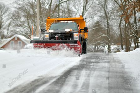 A Darien Town snowplow clears the road of new snow.