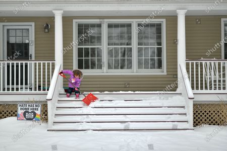 Riley Walker attempts to shovel the steps covered in new snow.