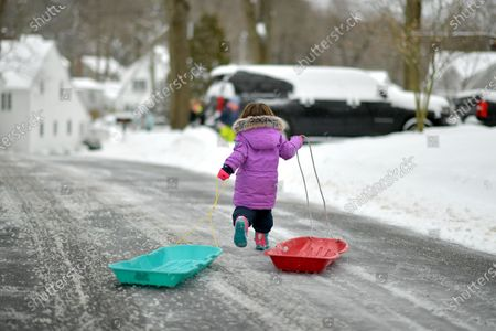 Riley Walker pulls two sleds down the street.