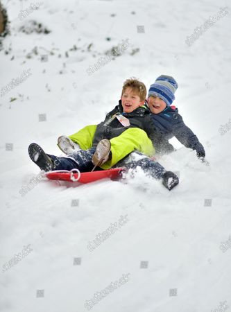 Stock Image of Kids sled in the new snow.