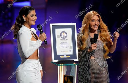 Chiquinquira Delgado, left, and Yuri present a certificate for the Guinness World Record for the longest running Latin music awards show in the United States for the Premio Lo Nuestro, held at American Airlines Arena, in Miami