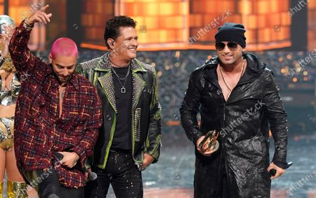 Maluma, from left, and Carlos Vives present the excellence award to Wisin at Premio Lo Nuestro at American Airlines Arena, in Miami