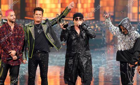Wisin, second right, accepts the Lo Nuestro Excellence Award at Premio Lo Nuestro at American Airlines Arena, in Miami. Presenting the award from left are Maluma, Carlos Vives and Rauw Alejandro