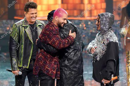 Maluma, center left, hugs Wisin, winner of the Lo Nuestro Excellence Award as Carlos Vives, left, and Rauw Alejandro look on at Premio Lo Nuestro at American Airlines Arena, in Miami