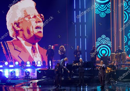 "Jose Alberto ""El Canario,"" from left, Nestor Torres and Gilberto Santarosa perform a tribute to Johnny Pacheco, pictured on screen, at Premio Lo Nuestro at American Airlines Arena, in Miami"
