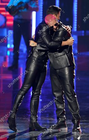 """Stock Photo of Carlos Rivera, left, and Maluma hug after performing """"100 Anos"""" at Premio Lo Nuestro at American Airlines Arena, in Miami"""