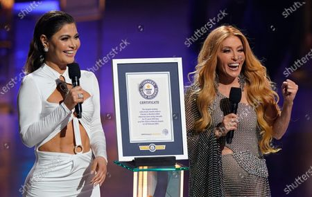 Stock Picture of Chiquinquira Delgado, left, and Yuri present a certificate for the Guinness World Record for the longest running Latin music awards show in the United States for the Premio Lo Nuestro, held at American Airlines Arena, in Miami