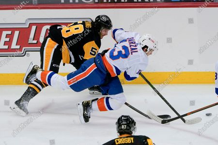 New York Islanders' Mathew Barzal (13) tumbles past Pittsburgh Penguins' Kris Letang (58) as they chase the puck during the third period of an NHL hockey game, in Pittsburgh