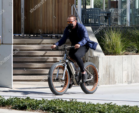 Stock Image of Arnold Schwarzenegger seen out for a bike ride on a sunny afternoon