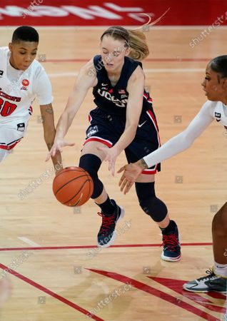 Connecticut guard Paige Bueckers, center, goes for a loose ball as she competes with St. John's guard Kadaja Bailey (30) and St. John's forward Raven Farley, right, during the second quarter of an NCAA college basketball game, at St. John's University in New York
