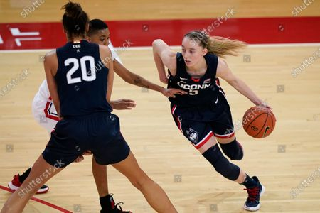 Connecticut guard Paige Bueckers (5) drives around St. John's guard Kadaja Bailey as Connecticut forward Olivia Nelson-Ododa (20) keeps Bailey from Bueckers during the second quarter of an NCAA college basketball game, at St. John's University in the Queens borough of New York