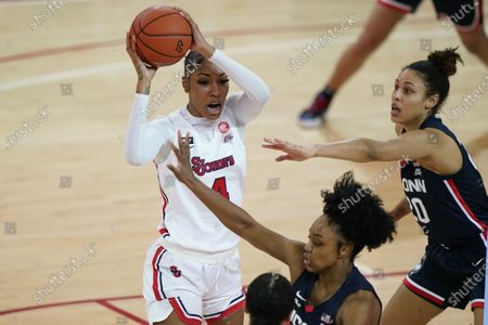 St. John's forward Raven Farley (4) looks to pass as Connecticut forward Olivia Nelson-Ododa (20) and Connecticut guard Christyn Williams, below, defend during an NCAA college basketball game, at St. John's University in the Queens borough of New York