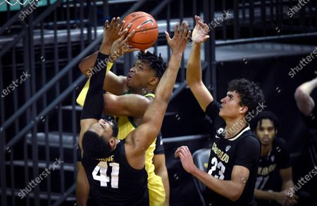 Oregon forward Chandler Lawson is fouled by Colorado forward Jeriah Horne (41) as he drives the lane past Colorado forward Tristan da Silva (23) during the first half of an NCAA college basketball game, in Eugene, Ore