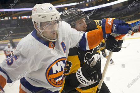 New York Islanders' Cal Clutterbuck (15) and Pittsburgh Penguins' Kris Letang (58) crash into the boards during the second period of an NHL hockey game, in Pittsburgh