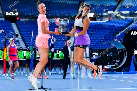 Elise Mertens of Belgium (L) and Aryna Sabalenka of Belarus jump into the air as they pose for photographs with the trophy after winning their Women's Doubles Finals match against Barbora Krejcikova of the Czech Republic and Katerina Siniakova of the Czech Republic on Day 12 of the Australian Open Grand Slam tennis tournament at Melbourne Park in Melbourne, Australia, 19 February 2021.