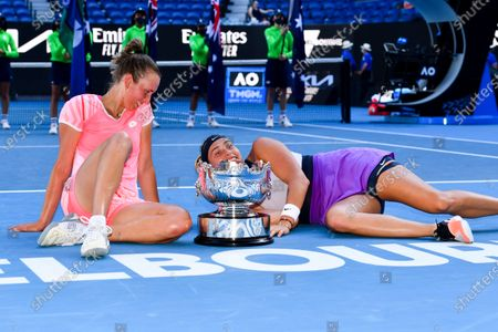 Elise Mertens of Belgium (L) and Aryna Sabalenka of Belarus pose for photographs with the trophy after winning their Women's Doubles Finals match against Barbora Krejcikova of the Czech Republic and Katerina Siniakova of the Czech Republic on Day 12 of the Australian Open Grand Slam tennis tournament at Melbourne Park in Melbourne, Australia, 19 February 2021.