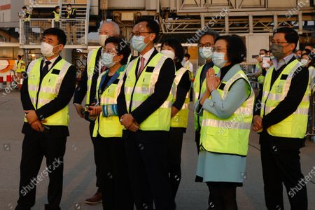 Secretary for Food and Health Sophia Chan Siu-chee (R) and Secretary for the Civil Service Patrick Nip Tak-kuen (2-R) observe containers carrying Sinovac Biotech coronavirus disease (COVID-19) vaccines being unloaded from a Cathay Pacific Airways aircraft at the Hong Kong, China, 19 February 2021.