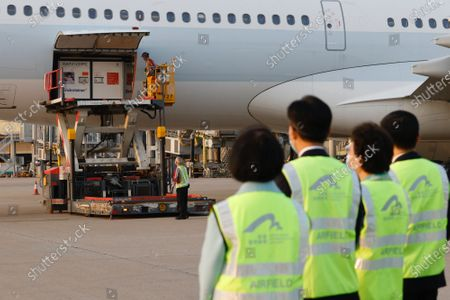 Secretary for Food and Health Sophia Chan Siu-chee (L) and Secretary for the Civil Service Patrick Nip Tak-kuen (2nd-L) observe containers carrying Sinovac Biotech coronavirus disease (COVID-19) vaccines are unloaded from a Cathay Pacific Airways aircraft at the Hong Kong, China, 19 February 2021.