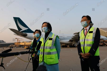 Secretary for Food and Health Sophia Chan Siu-chee (C) and Secretary for the Civil Service Patrick Nip Tak-kuen (R) speak to media after containers carrying Sinovac Biotech coronavirus disease (COVID-19) vaccines are unloaded from a Cathay Pacific Airways aircraft at the Hong Kong International Airport in Hong Kong, China, 19 February 2021.