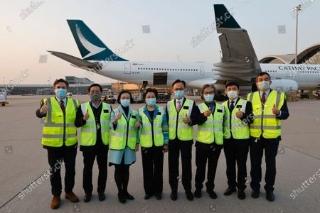 Secretary for Food and Health Sophia Chan Siu-chee (3rd-L) and Secretary for the Civil Service Patrick Nip Tak-kuen (4th-R) pose as containers carrying Sinovac Biotech coronavirus disease (COVID-19) vaccines are unloaded from a Cathay Pacific Airways aircraft at the Hong Kong, China, 19 February 2021.