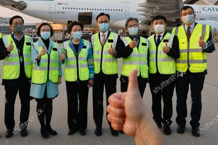 Secretary for Food and Health Sophia Chan Siu-chee (2-L) and Secretary for the Civil Service Patrick Nip Tak-kuen (4-R) pose as containers carrying Sinovac Biotech coronavirus disease (COVID-19) vaccines are unloaded from a Cathay Pacific Airways aircraft at the Hong Kong, China, 19 February 2021.