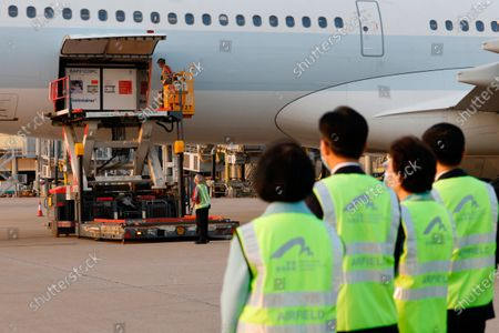 Secretary for Food and Health Sophia Chan Siu-chee, left, and Secretary for the Civil Service Patrick Nip Tak-kuen, second left, observe a container carrying Sinovac Biotech coronavirus disease (COVID-19) vaccines is unloaded from a Cathay Pacific Airways aircraft at the Hong Kong International Airport in Hong Kong . China's Sinovac delivered 1 million doses of its COVID-19 vaccine CoronaVac to Hong Kong on Friday evening