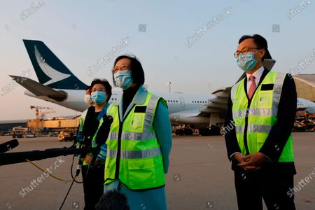 Stock Image of Secretary for Food and Health Sophia Chan Siu-chee, center, and Secretary for the Civil Service Patrick Nip Tak-kuen, right, speak to media after containers carrying Sinovac Biotech coronavirus disease (COVID-19) vaccines were unloaded from a Cathay Pacific Airways aircraft at the Hong Kong International Airport in Hong Kong, . China's Sinovac delivered 1 million doses of its COVID-19 vaccine CoronaVac to Hong Kong on Friday evening