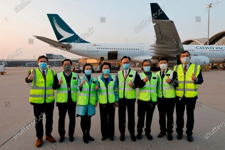 Secretary for Food and Health Sophia Chan Siu-chee, third left, and Secretary for the Civil Service Patrick Nip Tak-kuen, fourth right, pose as containers carrying Sinovac Biotech coronavirus disease (COVID-19) vaccines are unloaded from a Cathay Pacific Airways aircraft at the Hong Kong, China Thursdayy