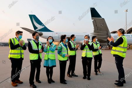 Stock Photo of Secretary for Food and Health Sophia Chan Siu-chee, third left, and Secretary for the Civil Service Patrick Nip Tak-kuen, fourth right, pose as containers carrying Sinovac Biotech coronavirus disease (COVID-19) vaccines are unloaded from a Cathay Pacific Airways aircraft in Hong Kong